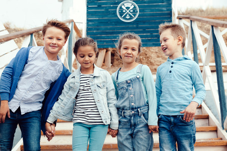 Foto de Group of fashion children wearing denim clothing having fun on the sea shore. Autumn casual outfit in blue and navy color. 7-8 years old models. - Imagen libre de derechos