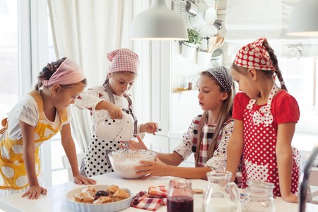 Photo pour Group of children cooking in the white kitchen. Kids wearing colorful aprons baking dessert at home. - image libre de droit