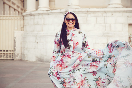 Foto de Plus size model wearing floral maxi dress posing on the city street. Young and fashionable overweight woman walking around town. - Imagen libre de derechos