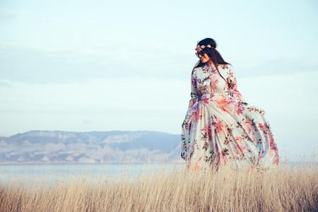 Woman wearing floral maxi dress posing in field.