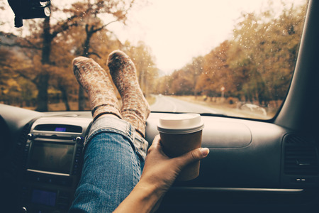 Woman feet in warm socks on car dashboard. Drinking take away coffee on road. Fall trip. Rain drops on windshield. Freedom travel concept. Autumn weekend. Filtered photo.