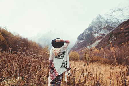 Photo pour Boho woman wearing hat and poncho standing by the mountain. Cold weather, snow on hills. Winter hiking. Wanderlust. - image libre de droit