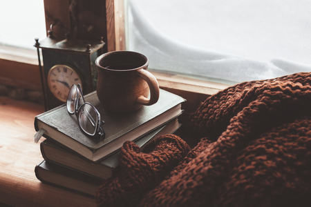 Foto de Warm and comfy winter concept. Book, cup of tea and sweater on wooden window sill in old house. Reading and relaxing in cold snowy weather at home. Quiet silent homely scene. - Imagen libre de derechos
