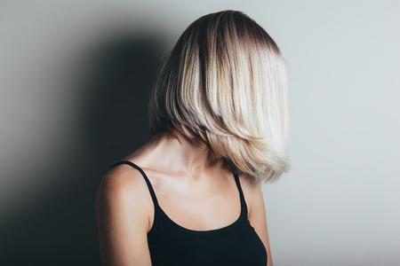 Foto de Model with unrecognizable face with blond shiny hair. Woman bob haircut styling. - Imagen libre de derechos