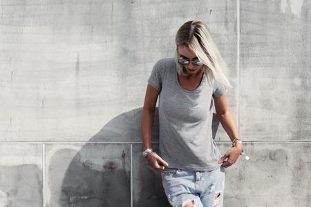 Foto de Hipster girl wearing blank t-shirt, fashion sunglasses and jeans posing against rough concgrete wall, minimalist street style - Imagen libre de derechos