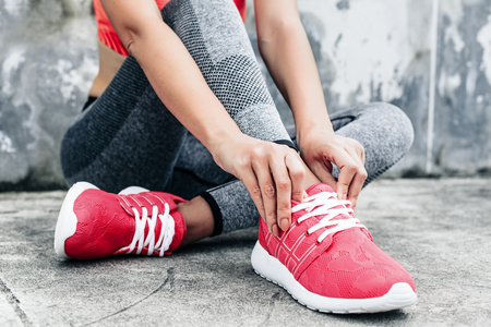 Foto de Fitness sport woman in fashion sportswear doing yoga fitness exercise in the city street over gray concrete background. Outdoor sports clothing and shoes, urban style. Tie sneakers. - Imagen libre de derechos
