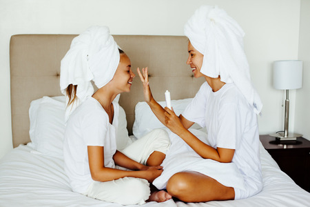 Photo for Mom and her 10 years old preteen child relaxing in the bedroom after shower. Mother applying blemish cream on her daughter face. Family beauty treatment. Morning care routine. Teenage skin problems. - Royalty Free Image