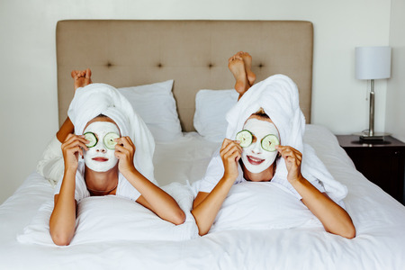 Foto de Mom and her 10 years old preteen daughter chilling in the bedroom and making clay facial mask. Mother with child doing beauty treatment together. Morning skin care routine. - Imagen libre de derechos