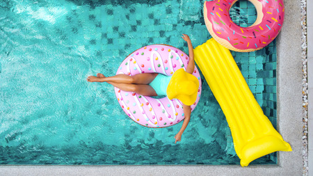 Photo pour Woman relaxing on donut lilo in the pool at private villa. Inflatable ring and mattress. Summer holiday idyllic. High view from above. - image libre de droit
