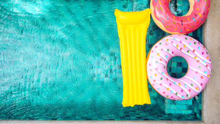 Photo for Donut lilo in the poolside at private villa. Inflatable ring and mattress. Summer holiday idyllic. High view from above. - Royalty Free Image