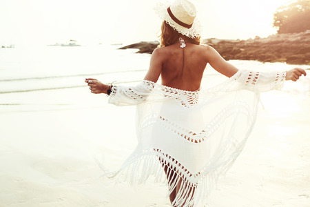Photo pour Beautiful boho styled model wearing white crochet swimsuit posing on the beach in sunlight - image libre de droit