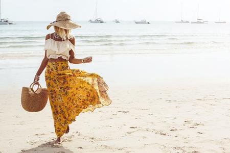 Photo for Girl wearing floral maxi skirt walking barefoot on the sea shore, Thailand, Phuket. Bohemian clothing style. - Royalty Free Image