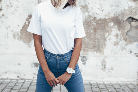 Foto per Hipster girl wearing blank white t-shirt and jeans posing against rough street wall, minimalist urban clothing style, mockup for tshirt print store - Immagine Royalty Free