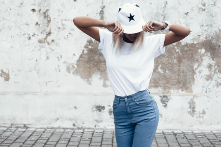 Foto de Hipster girl wearing blank white t-shirt, jeans and baseball cap posing against rough street wall, minimalist urban clothing style, mock up for tshirt print store - Imagen libre de derechos