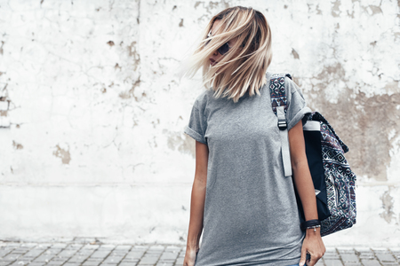 Hipster girl wearing blank gray t-shirt and backpack posing against rough street wall, minimalist urban clothing style, mock up for tshirt print store