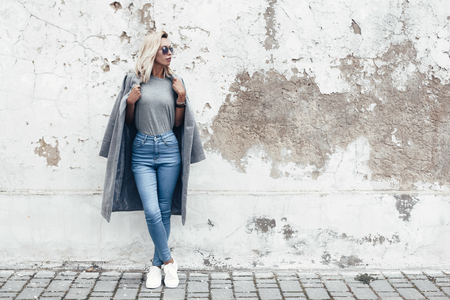 Photo for Hipster girl wearing blank gray t-shirt, jeans and coat posing against rough street wall, minimalist urban clothing style, mockup for tshirt print store - Royalty Free Image
