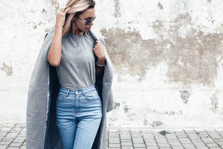 Foto de Hipster girl wearing blank gray t-shirt, jeans and coat posing against rough street wall, minimalist urban clothing style, mockup for tshirt print store - Imagen libre de derechos