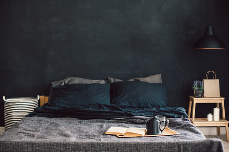 Black stylish loft bedroom. Unmade bed with breakfast and reading on tray. Lamp and interior decor over blank blackboard wall with copyspace. Cozy modern living space.