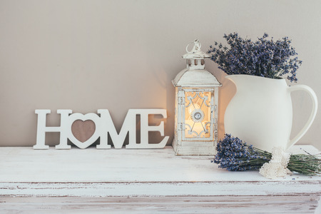 Foto de Shabby chic interior decor for farmhouse. Lavender in pitcher, lantern and wooden letters on a vintage shelf over pastel wall. Provence home decoration. - Imagen libre de derechos
