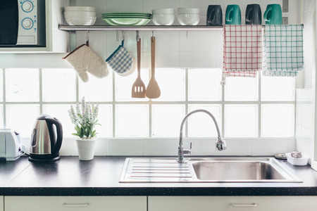 Photo pour Home kitchen interior. Cooking utensils on a railing system and shelf with dishes above a window. - image libre de droit