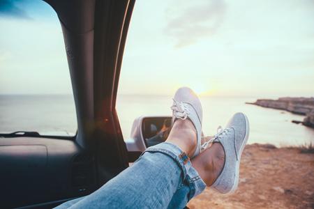Fall car trip in sunset. Freedom travel concept. Spending weekend in roadtrip. Woman feet on car window, wathing the sea.