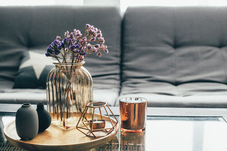 Photo for Home interior decor in gray and brown colors: glass jar with dried flowers, vase and candle on the wooden tray on the coffee table over sofa with cushions. Living room decoration. - Royalty Free Image