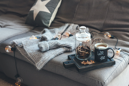 Still life details of living room. Cup of coffee on rustic wooden tray, candle and warm woolen sweater on sofa, decorated with led lights. Autumn weekend concept. Fall home decoration.
