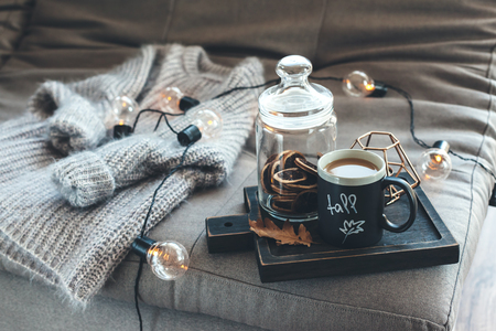 Foto de Still life details of living room. Cup of coffee on rustic wooden tray, candle and warm woolen sweater on sofa, decorated with led lights. Autumn weekend concept. Fall home decoration. - Imagen libre de derechos