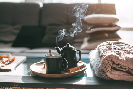 Still life details in home interior of living room. Sweaters and cup of tea with steam on a serving tray on a coffee table. Breakfast over sofa in morning sunlight. Cozy autumn or winter concept.の素材 [FY31085981991]