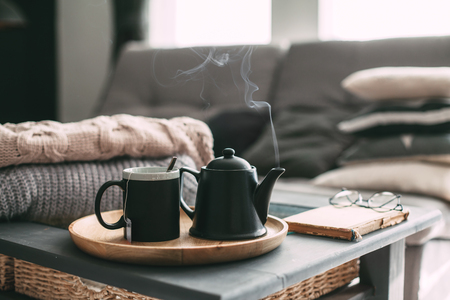 Foto de Still life details in home interior of living room. Sweaters and cup of tea with steam on a serving tray on a coffee table. Breakfast over sofa in morning sunlight. Cozy autumn or winter concept. - Imagen libre de derechos