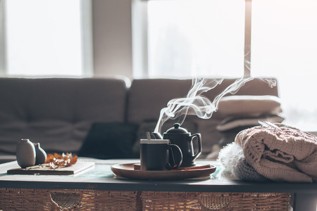 Photo for Still life details in home interior of living room. Sweaters and cup of tea with steam on a serving tray on a coffee table. Breakfast over sofa in morning sunlight. Cozy autumn or winter concept. - Royalty Free Image