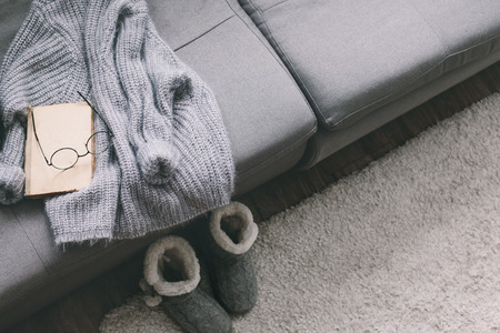 Cashmere sweater and reading on gray sofa. Warm weekend at home. Detail of cozy winter interior.
