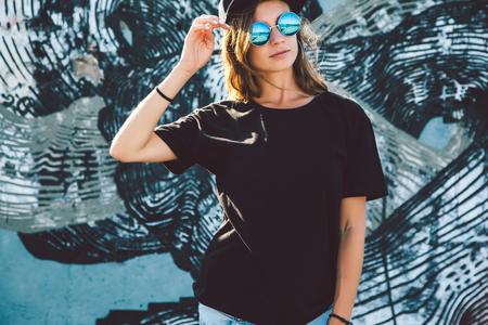Foto de Model wearing plain black t-shirt and hipster sunglasses posing against street wall, teen urban clothing style, mockup for tshirt print store - Imagen libre de derechos