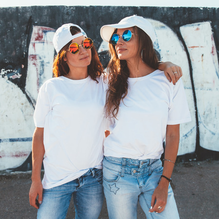 Foto de Two models wearing plain white t-shirts and hipster sunglasses posing against street wall. Teen urban clothing style, same look. Mockup for tshirt print store. - Imagen libre de derechos