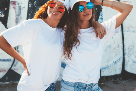 Photo pour Two models wearing plain white t-shirts and hipster sunglasses posing against street wall. Teen urban clothing style, same look. Mockup for tshirt print store. - image libre de droit