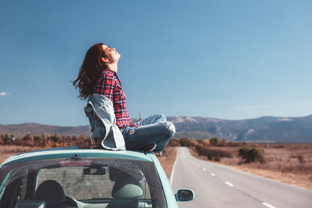Photo pour Hipster girl relaxing on the car roof in her autumn road trip, carefree and enjoying freedom and travel. Wanderlust concept scene. - image libre de droit