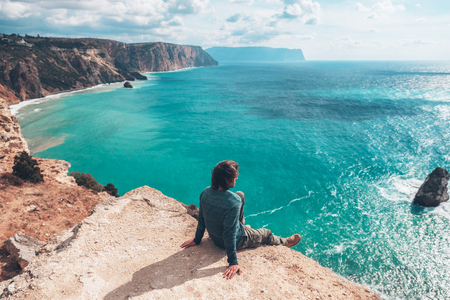 Photo pour Man traveler sitting on mountain alone and looking at autumn sea landscape. Hiking in cold season. Wanderlust concept scene. - image libre de droit