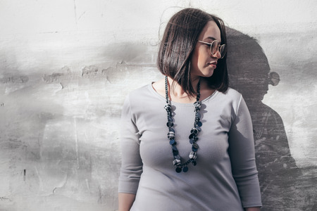 Photo pour Plus size model with bob haircut wearing minimalist gray maxi dress, sunglasses and jewelry posing over street wall. - image libre de droit