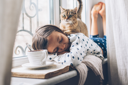 Foto de Child in pajamas relaxing on a window sill with pet. Lazy weekend with cat at home. Cozy scene, hygge concept. - Imagen libre de derechos