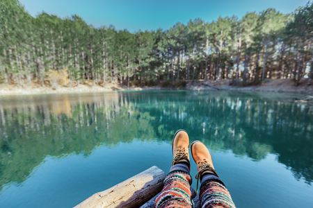 Photo pour Woman relaxing in by the lake in the forest, POV view of legs in trekking boots. Hiking in cold season. Wanderlust concept scene. - image libre de droit