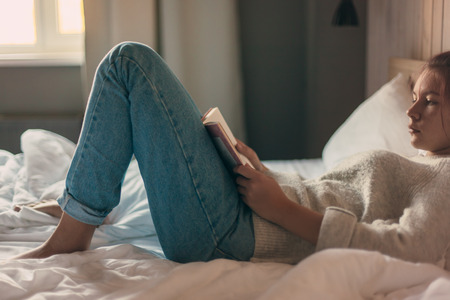 Foto per Teen girl in sweater reading a book in a hotel bedroom in the morning - Immagine Royalty Free