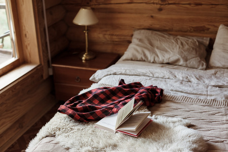 Photo pour Rustic interior of log cabin bedroom with bed by big window. Opened book on sheep rug. Warm and cozy weekend morning in hotel. - image libre de droit