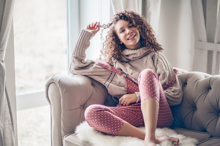 Photo pour Hipster teenage girl with curly hair wearing beige knitted sweater and pink polka dot jumpsuit relaxing on a couch indoor - image libre de droit