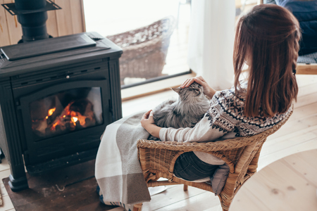 Foto de Human with cat relaxing in wicker armchair by the fire place in wooden cabin. Warm and cozy winter holiday concept. - Imagen libre de derechos