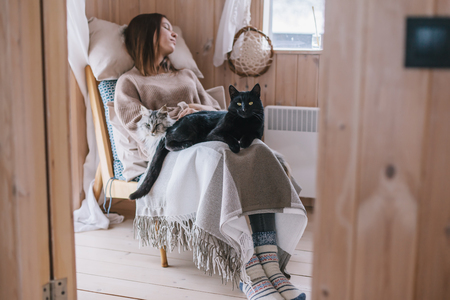 Foto de Young girl in sweater with cat sleeping on chair in log cabin near window - Imagen libre de derechos