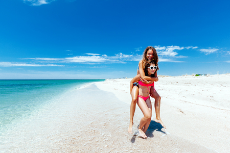 Photo pour Teenage friends having fun on the beach. Summer vacations by the sea. - image libre de droit