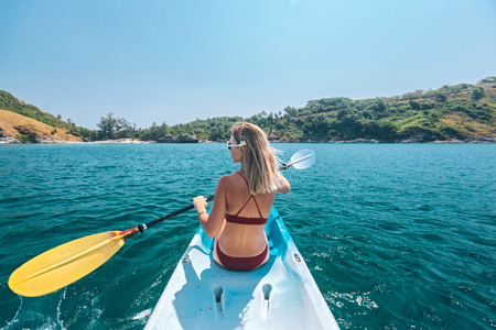 Photo pour Woman paddling a kayak by the tropical beach. Kayaking tour in Phuket, Thailand - image libre de droit