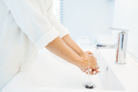 Foto de Closeup photo of person washing hands in white clean basin in home washroom - Imagen libre de derechos
