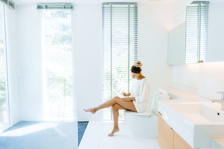 Photo pour Photo of woman applying body lotion to her legs after shower in luxury bathroom - image libre de droit