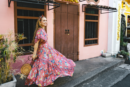 Foto de Boho girl in maxi dress and straw hat walking on the Asia city street. Travelling in Phuket Old Town in Thailand. - Imagen libre de derechos